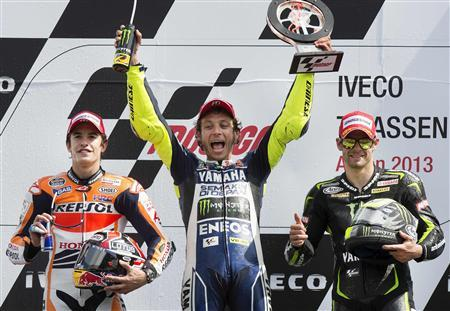 Yamaha MotoGP riders Cal Crutchlow of Britain and Valentino Rossi of Italy (C), and Honda MotoGP rider Marc Marquez of Spain (L) celebrate on the podium after the Dutch Grand Prix in Assen June 29, 2013. REUTERS/Paul Vreeker/United Photos